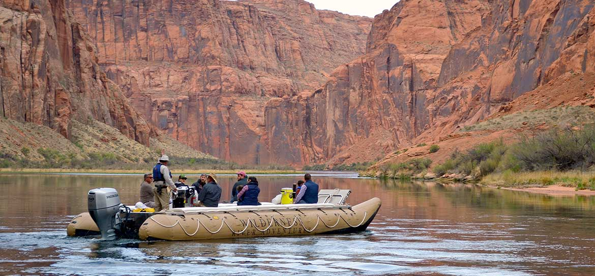 Several people aboard a raft on the Colorado River