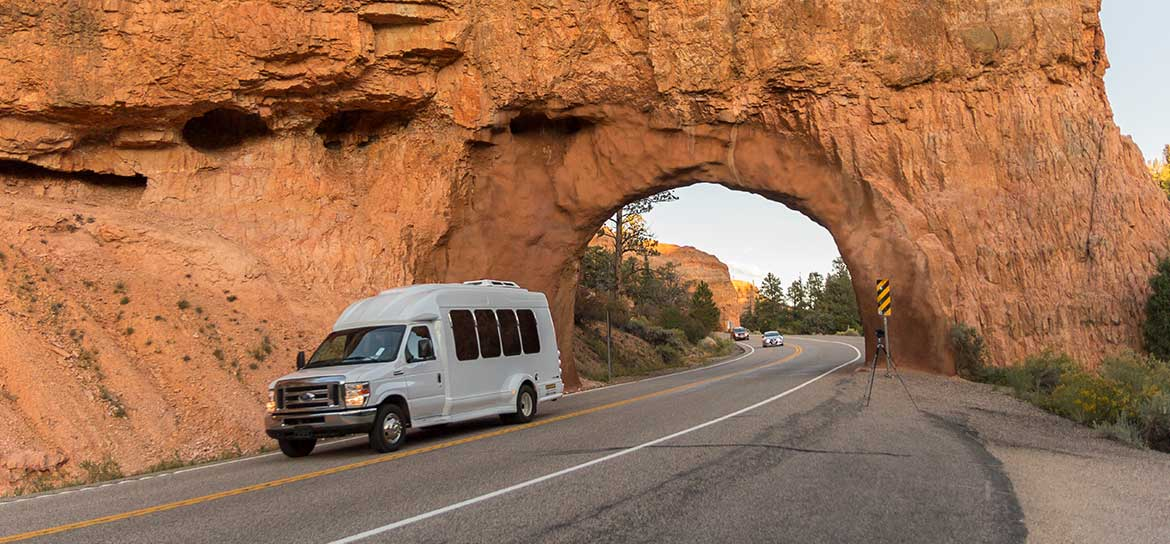 A van drives through a desert canyon